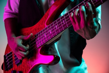 African American handsome jazz musician playing bass guitar in the studio on a neon background. Music concept. Young joyful attractive guy improvising. Close-up retro portrait. Banque d'images - 119324854