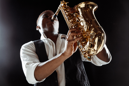 African American handsome jazz musician playing the saxophone in the studio on a black background. Music concept. Young joyful attractive guy improvising. Close-up retro portrait.