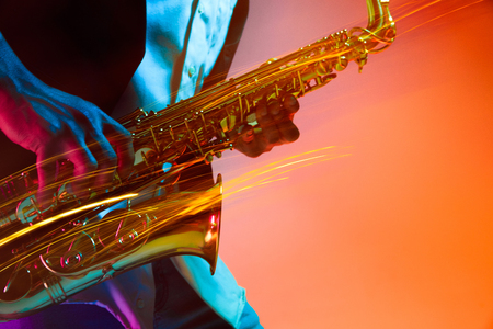 African American handsome jazz musician playing the saxophone in the studio on a neon background. Music concept. Young joyful attractive guy improvising. Close-up retro portrait. Foto de archivo