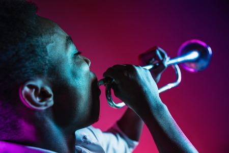 African American handsome jazz musician playing trumpet in the studio on a neon background. Music concept. Young joyful attractive guy improvising. Close-up retro portrait.