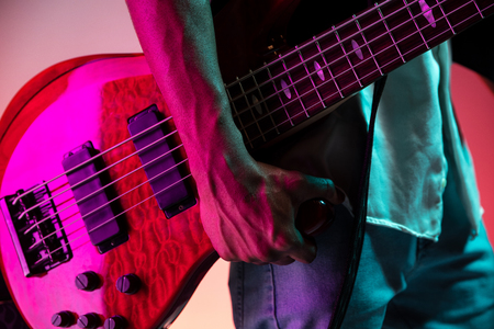 African American handsome jazz musician holding bass guitar in the studio on a neon background. Music concept. Close-up retro portrait. Banque d'images - 119324955