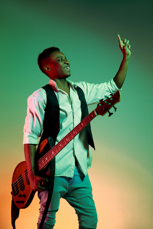 African American handsome jazz musician holding bass guitar and welcomes the audience. Music concept. Young joyful attractive guy improvising. Close-up retro portrait in the studio on a neon background.