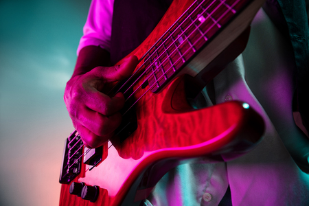 African American handsome jazz musician playing bass guitar in the studio on a neon background. Music concept. Young joyful attractive guy improvising. Close-up retro portrait. Banque d'images - 119324999