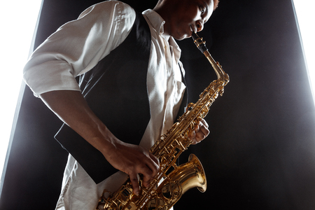 African American handsome jazz musician playing the saxophone in the studio on a black background. Music concept. Young joyful attractive guy improvising. Close-up retro portrait. Stock Photo - 119324985