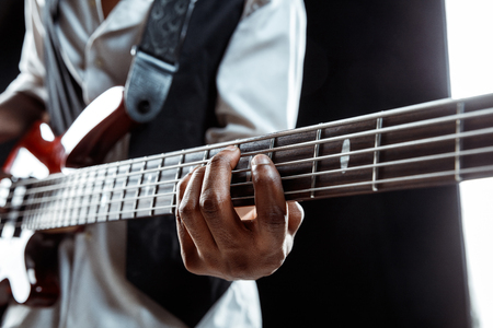 African American handsome jazz musician playing bass guitar in the studio on a black background. Music concept. Young joyful attractive guy improvising. Close-up retro portrait. 写真素材