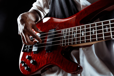 African American handsome jazz musician playing bass guitar in the studio on a black background. Music concept. Young joyful attractive guy improvising. Close-up retro portrait. Banque d'images - 119325093