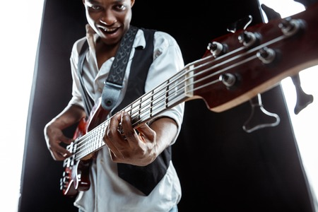 African American handsome jazz musician playing bass guitar in the studio on a black background. Music concept. Young joyful attractive guy improvising. Close-up retro portrait. Banque d'images - 119325118
