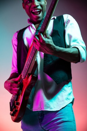 African American handsome jazz musician playing bass guitar in the studio on a neon background. Music concept. Young joyful attractive guy improvising. Close-up retro portrait. Banque d'images - 119325245