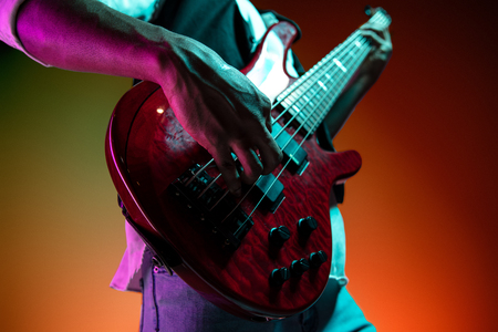 African American handsome jazz musician playing bass guitar in the studio on a neon background. Music concept. Young joyful attractive guy improvising. Close-up retro portrait. Banque d'images - 119325252