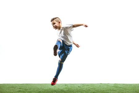Young boy running and jumping isolated on white studio background. Junior football soccer player in motion Stock Photo