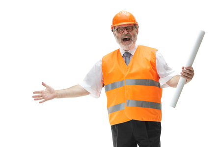 The happy builder in a construction vest and an orange helmet smiling at studio. Safety specialist, engineer, industry, architecture, manager, occupation, businessman, job concept Imagens