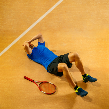 Stressed tennis player looking defeated and sad, he screaming in rage at court. Human emotions, defeat, crash, failure, loss concept