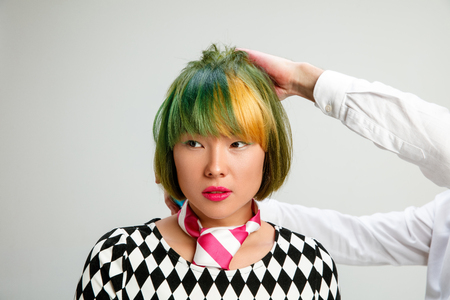 Picture showing adult woman at the hair salon. Studio shot of graceful young girl with stylish short haircut and colorful hair on gray background. Hands of hairdresser close up. Stock Photo