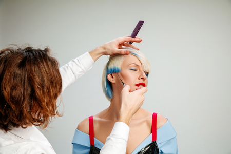 Picture showing adult woman at the hair salon. Studio shot of graceful young girl with stylish short haircut and colorful hair on gray background and hands of hairdresser. Stock Photo