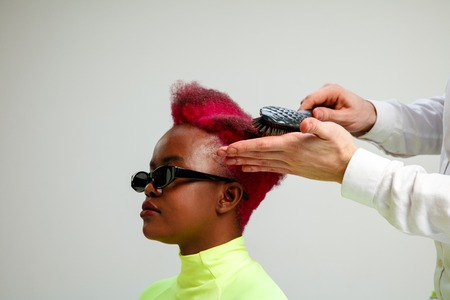 Picture showing african american woman at the hair salon. Studio shot of graceful young girl with stylish short haircut and colorful hair on gray background and hands of hairdresser. Stock Photo