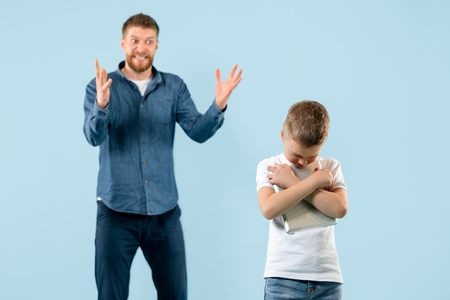 Angry father scolding his son at home. Studio shot of emotional family. Human emotions, childhood, problems, conflict, domestic life, relationship concept Stock Photo - 119577598