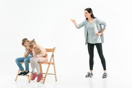 Angry mother scolding her son and daughter at home. Studio shot of emotional family. Human emotions, childhood, problems, conflict, domestic life, relationship concept Foto de archivo - 119578077