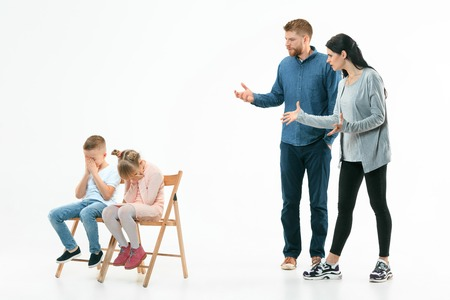 Angry parents scolding their children - son and daughter at home. Studio shot of emotional family. Human emotions, childhood, problems, conflict, domestic life, relationship concept Foto de archivo - 119578175
