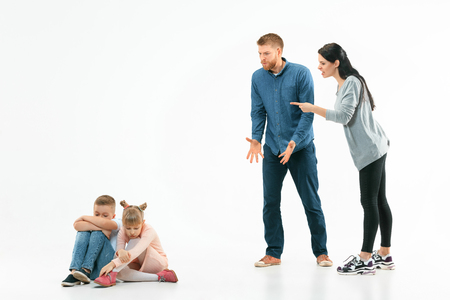 Angry parents scolding their children - son and daughter at home. Studio shot of emotional family. Human emotions, childhood, problems, conflict, domestic life, relationship concept