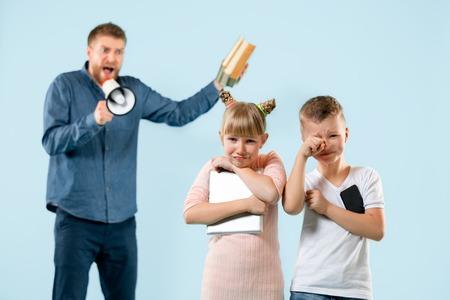 Verärgerter Vater, der seinen Sohn und seine Tochter zu Hause schimpft Studioaufnahme einer emotionalen Familie. Menschliche Emotionen, Kindheit, Probleme, Konflikte, häusliches Leben, Beziehungskonzept Standard-Bild