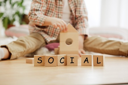 Wooden cubes with word SOCIAL in hands of little boy at home. Conceptual image about child rights, education, childhood and social problems. Stock Photo