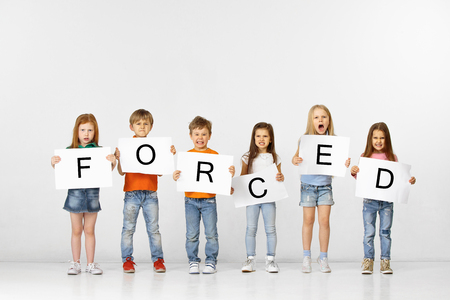 Being forced is prison. Group of angry screaming children with a white banners holding word isolated in studio background. Education, advertising and social rights concept.