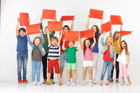 Groupe d'enfants qui crient heureux avec des bannières vides rouges isolées sur fond de studio blanc. Concept d'éducation et de publicité. Concepts de protestation et de droits de l'enfant. Banque d'images