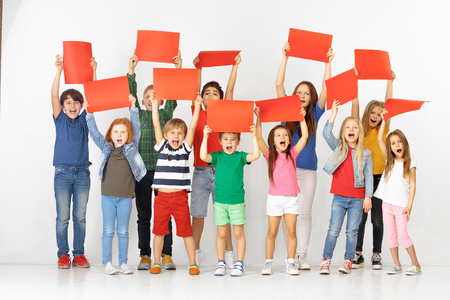 Grupo de niños felices gritando con un rojo banderas vacías aisladas en el fondo blanco del estudio. Concepto de educación y publicidad. Conceptos de protesta y derechos del niño. Foto de archivo