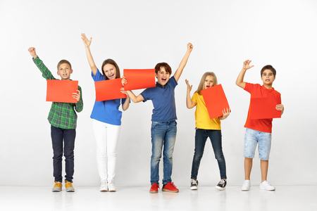 Group of happy smiling children with red empty banners isolated in white studio background. Education and advertising concept Stockfoto
