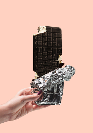 Delicious text - wanna bite the word. Chocolate bar with creamy filling as a keyboard. Female hand holding sweets. Copywriting concept. Negative space. Modern design. Contemporary art collage.
