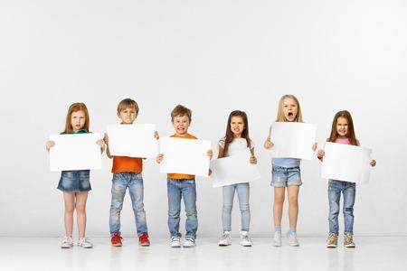 Groep boze kinderen met witte lege banners die op witte studioachtergrond worden geïsoleerd. Onderwijs en reclame concept. Protest en kinderrechten concepten.