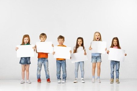 Group of angry children with a white empty banners isolated in white studio background. Education and advertising concept. Protest and childrens rights concepts.