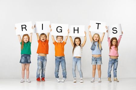 All people have rights. Group of happy smiling and screaming children with a white banners making word isolated in studio background. Education, advertising and social right concept. Stockfoto - 119890832