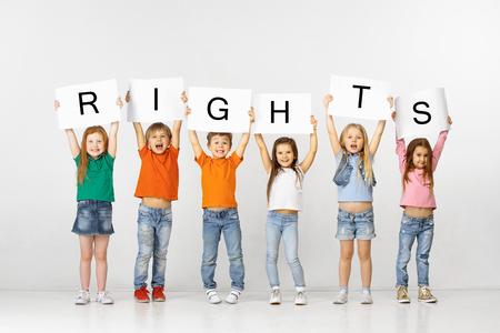 Todas las personas tienen derechos. Grupo de niños felices sonriendo y gritando con pancartas blancas haciendo palabra aislada en el fondo del estudio. Concepto de educación, publicidad y derechos sociales.