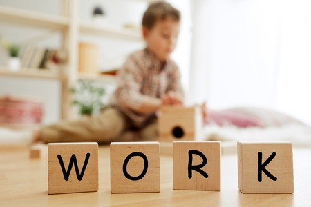 Wooden cubes with word WORK in hands of happy smiling little boy at home. Conceptual image about child rights, education, childhood and social problems.