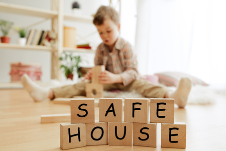 Wooden cubes with words SAFE HOUSE in hands of happy smiling little boy at home. Conceptual image about child rights, education, childhood and social problems. Stock Photo - 119814323