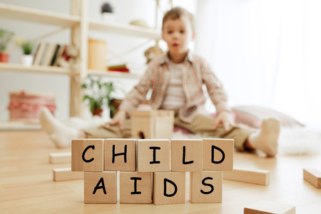 Wooden cubes with words CHILD AIDS in hands of little boy at home. Symbol of the fight against HIV, AIDS and cancer. Concept of helping those in need Reklamní fotografie