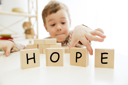 Wooden cubes with word HOPE in hands of happy smiling little boy at home. Conceptual image about child rights, education, childhood and social problems.