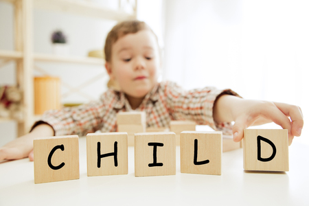 Wooden cubes with words CHILD in hands of smiling little boy at home. Conceptual image about child rights, education, childhood and social problems.