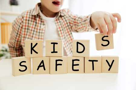 Wooden cubes with words KIDS SAFETY in hands of little boy at home. Conceptual image about child rights, education, childhood and social problems.