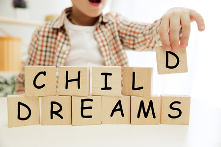 Wooden cubes with words CHILD DREAMS in hands of happy smiling little boy at home. Conceptual image about child rights, education, childhood and social problems.