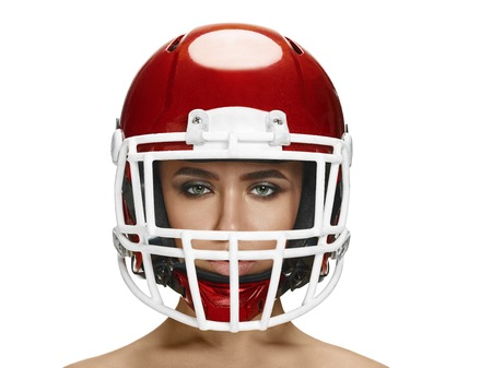 American football theme. Young beautiful woman in helmet isolated on white. Skin protection concept Stock Photo