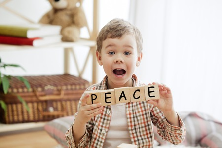 Wooden cubes with word PEACE in hands of happy smiling little boy at home. Conceptual image about child rights, education, childhood and social problems. Stock fotó