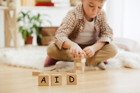 Wooden cubes with word AID in hands of little boy at home. Symbol of the fight against HIV, AIDS and cancer. Concept of helping those in need Stock Photo - 119596928