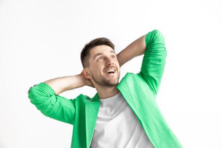 À la recherche du meilleur moment. Jeune homme souriant rêvant attend des chanses isolées sur fond gris. Rêveur au studio en T-shirt blanc Banque d'images