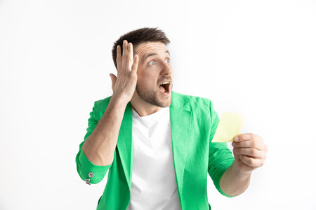 Young caucasian man with a surprised happy expression won a bet on gray studio background. Human facial emotions and betting concept Stock fotó - 119596441