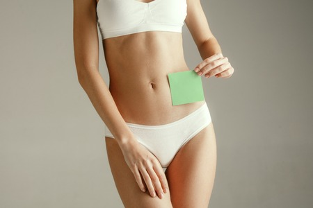 Woman health. Female model holding empty card near stomach. Young adult girl with paper for sign or symbol isolated on gray studio background. Cut out part of body. Medical problem and solution. Stockfoto - 119596704