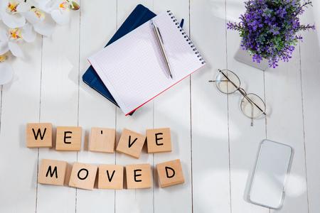 NOUS AVONS DÉMÉNAGÉ. Message à cubes en bois sur un fond de bureau. Mode de vie, affaires, bureau, motivation, plan, succès, objectif et concept de gestion. Vue de dessus ou à plat.