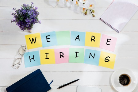 WE ARE HIRING. Message at colorful note papers on a desk background. Lifestyle, business, office, motivation, plan, success, goal and management concept. Top or flat lay view..