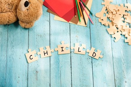 Stationery and word CHILD made of letters, mock up and pieces of puzzles on wooden background. Concept of family, baby, pregnancy, maternity, parenting, children. Foto de archivo - 119757827